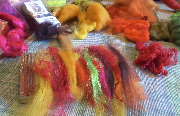 a palette of coloured fibres on a carder